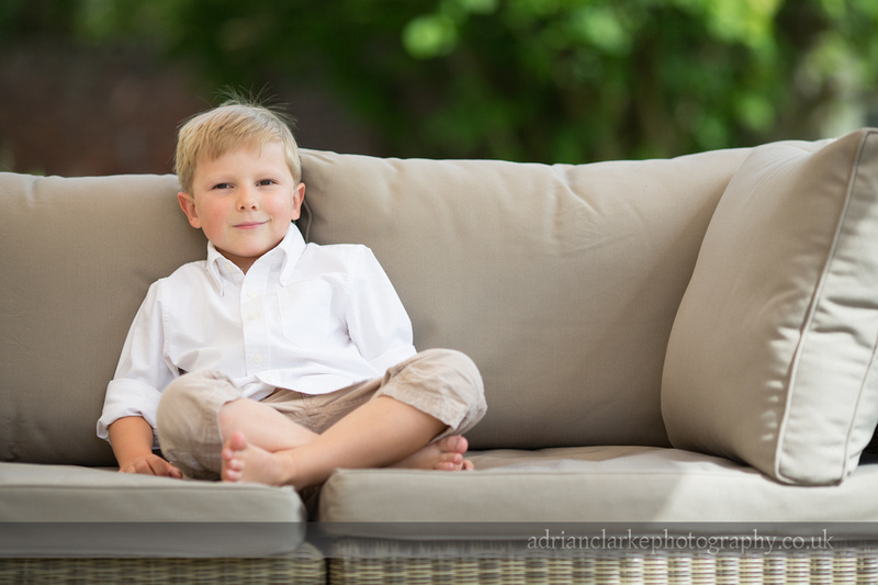 portrait photograph of young boy on sofa smiling